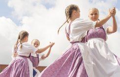 Kuvassa tytöt tanssivat letit liehuen.