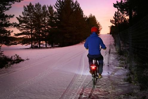 Pyöräilija ajaa lumisella tiellä.